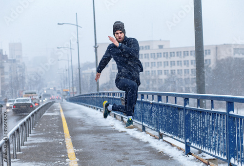 Obraz Young man running in city street at cold winter day. - fototapety do salonu
