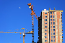 Two High-rise Construction Cranes And Unfinished Monolithic Building On The Blue Sky Background. Building Construction Site With Cranes. The Construction Of Modern Apartment Buildings