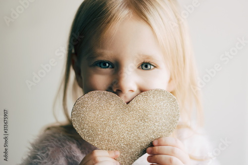 Obraz Valentines day. Little girl with a heart. Portrait of a little girl holding valentine's card. - fototapety do salonu