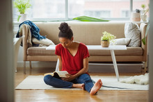 Woman Reading Book While Sitting On Floor At Home