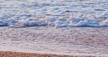 Tilting From The Blue Summer Sky Across The Sea With Waves To A Sandy Beach Covered With Shells
