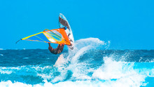 Watersports: Windsurfer Have Fun Making An Acrobatic Jump In The Waves