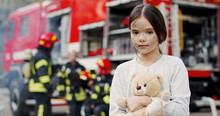 Portrait Of Saved Little Asian Girl Standing Near Fire Truck. Firefighter In Fire Fighting Operation