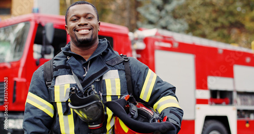 Firefighter portrait on duty. Photo of happy fireman with gas mask and helmet near fire engine