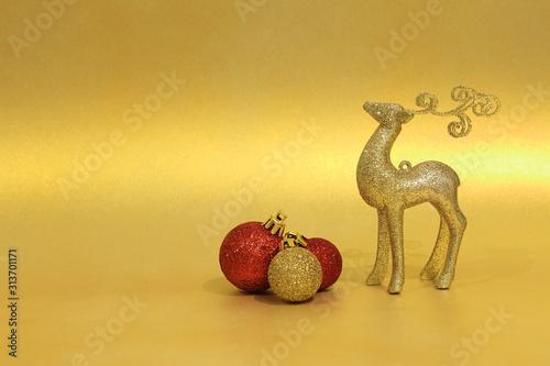 Obraz Figurka złotego jeloneka i bombki choinkowe na złotym tle, Boże Narodzenie. - fototapety do salonu