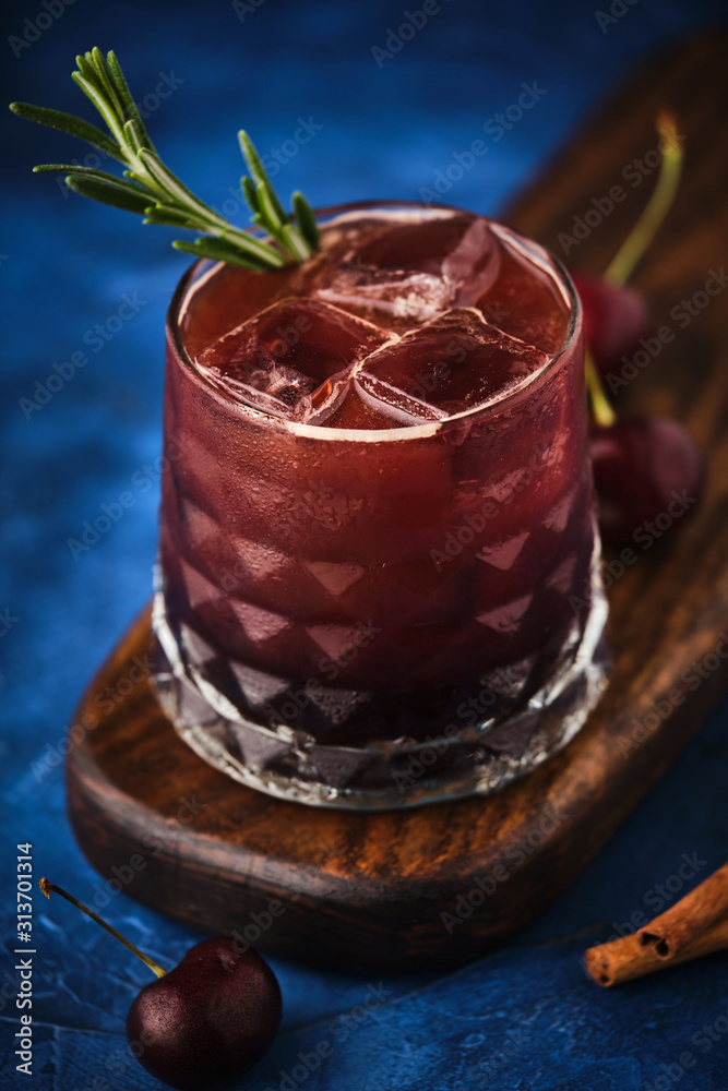 Fototapeta Cherry cocktail with rosemary and cinnamon.