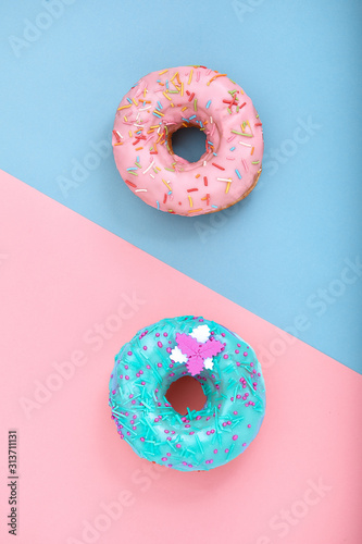 Two donuts on pastel pink and blue background. Minimalism creative food composition. Flat lay style