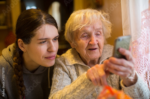 Fotomural An elderly old woman looks at a smartphone his adult granddaughter