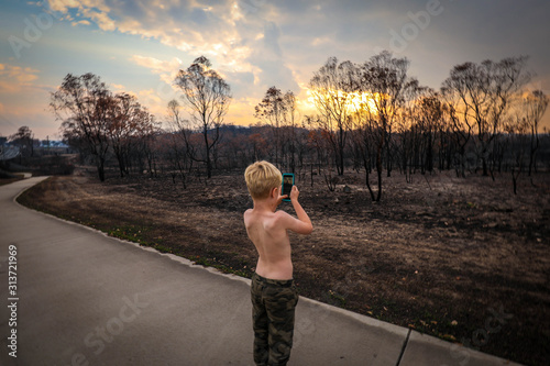 Photo Young boy taking photos of aftermath of the 2019/2020 bushfire season in New Sou