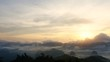 Time-lapse of sunrise mist and cloudscape moving on mountain.