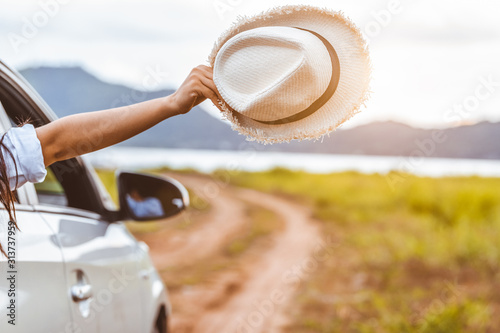 Obraz Happy woman hand holding hat outside open window car with meadow and mountain lake background. People lifestyle relaxing as traveler on road trip in holiday vacation. Transportation and travel concept - fototapety do salonu