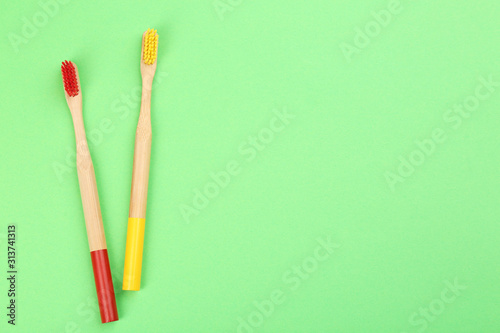 Fotografie, Obraz  Natural bamboo toothbrushes on green background, flat lay