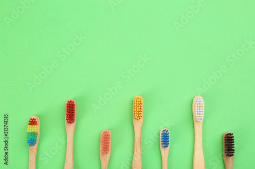 Fototapeta  Natural toothbrushes made with bamboo on green background, flat lay