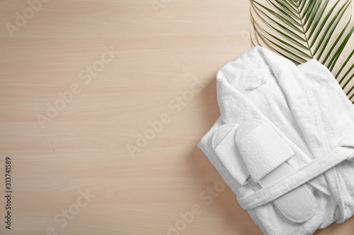 Obraz Clean folded bathrobe and slippers on wooden background, flat lay. Space for text - fototapety do salonu