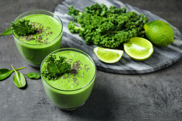 Tasty kale smoothie with chia seeds on grey table