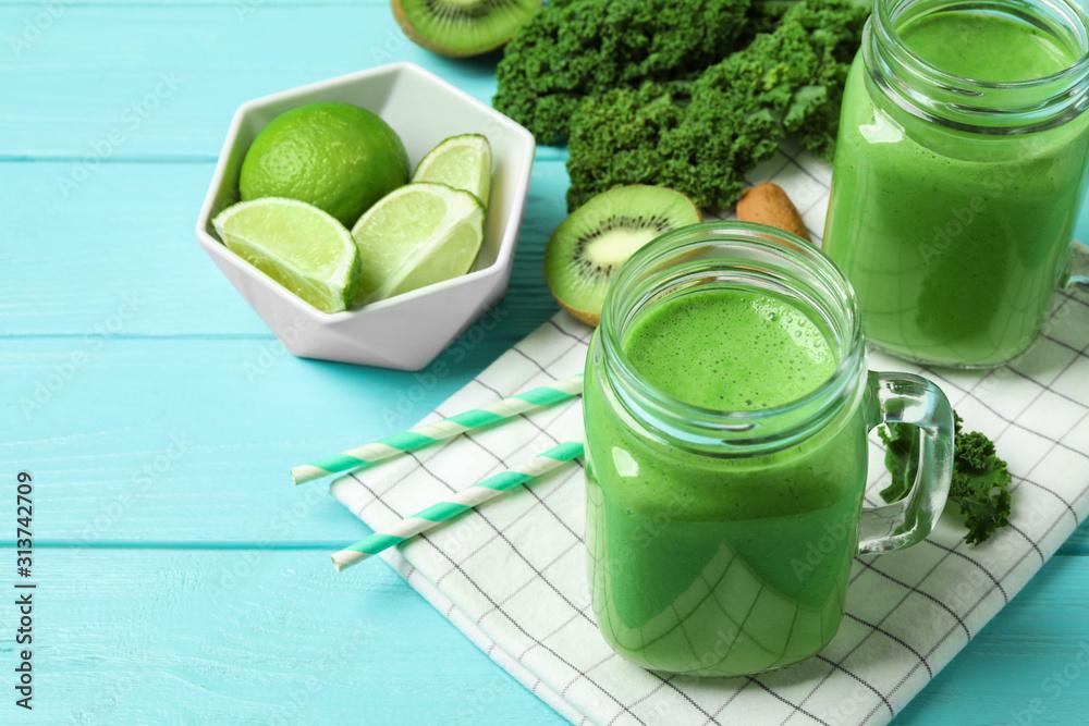 Fototapeta Tasty fresh kale smoothie on light blue wooden table