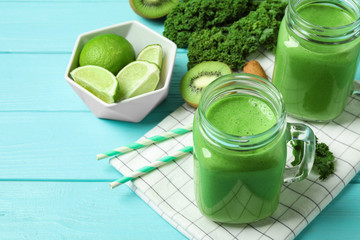 Tasty fresh kale smoothie on light blue wooden table