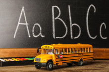 School Bus Model And Stationery On Wooden Table Near Chalkboard. Transport For Students