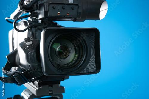 Vászonkép Professional video camera on blue background, closeup