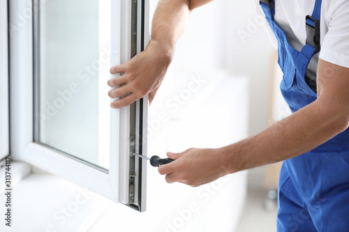 Construction worker repairing plastic window with screwdriver indoors, closeup Canvas