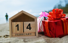 Happy Valentines Day Concept, Wooden Calendar On February 14, Red Gift Box In Soft Focus Background.