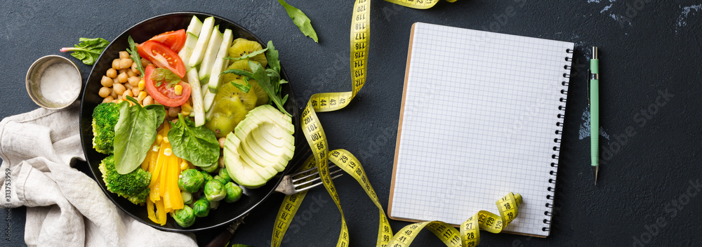 Fototapeta Vegan healthy balanced diet. Vegetarian buddha bowl with blank notebook and measuring tape. Сhickpeas, broccoli, pepper, tomato, spinach, arugula and avocado in plate on dark background. Top view