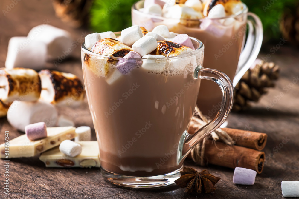 Obraz Hot cocoa or chocolate with marshmallow in glass mug and winter decoration on wooden table. Concept of cosy Christmas holidays and New Year, copy space fototapeta, plakat