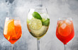 canvas print picture - Set of summer Italian alcoholic cocktails, aperol spritz, martini royale, campari tonic with bitters and prosecco in misted wine glasses. Close-up, selective focus