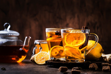Hot healing tea with ginger, honey, lemon and spices in glass cup, rustic wooden background copy space