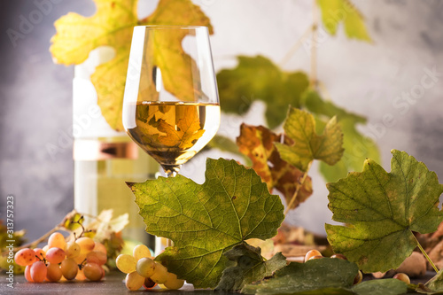 Obraz White wine glass and wine bottle on gray background with copy space - fototapety do salonu