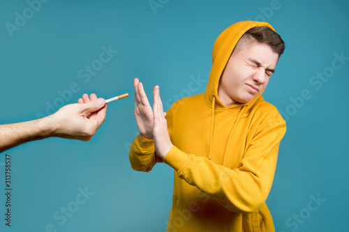 Fototapeta a teenager in a yellow sweatshirt on a blue background shows disgust when they h