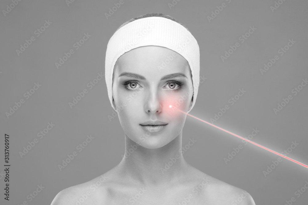 Fototapeta Doctor removing birthmarks with a laser ray. Beautiful face of a young woman. Mole removal, plastic surgery, skin lifting and aesthetic medicine.