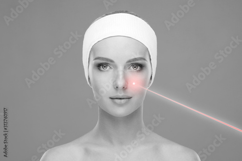 Obraz Doctor removing birthmarks with a laser ray. Beautiful face of a young woman. Mole removal, plastic surgery, skin lifting and aesthetic medicine. - fototapety do salonu