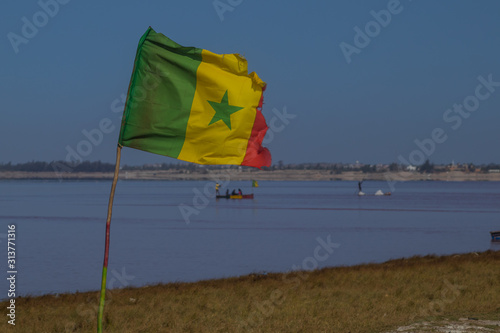 Fényképezés  SenegaleSenegalese flag on Lac Rose or Lake Retba in Senegal