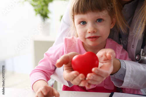 Canvastavla  Little baby girl visiting doctor holding in hands red toy heart