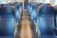 Blue Lined Seats Lined Up Along The Corridor Of A Regional Train With No Passengers During The Day