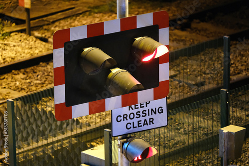 Valokuva Railway level crossing in town centre at night.