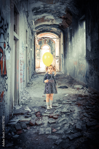 blonde girl with a balloon inside a decadent and abandoned building.