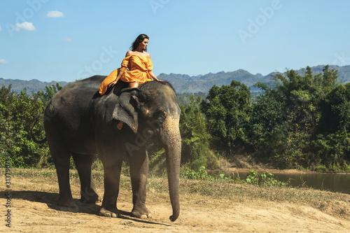 Photo Woman wearing beautiful orange dress is riding the elephant