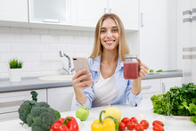 Cute Blonde Girl Drinking Smoothie In A Light Kitchen Full Of Vegetables And Making A Selfie