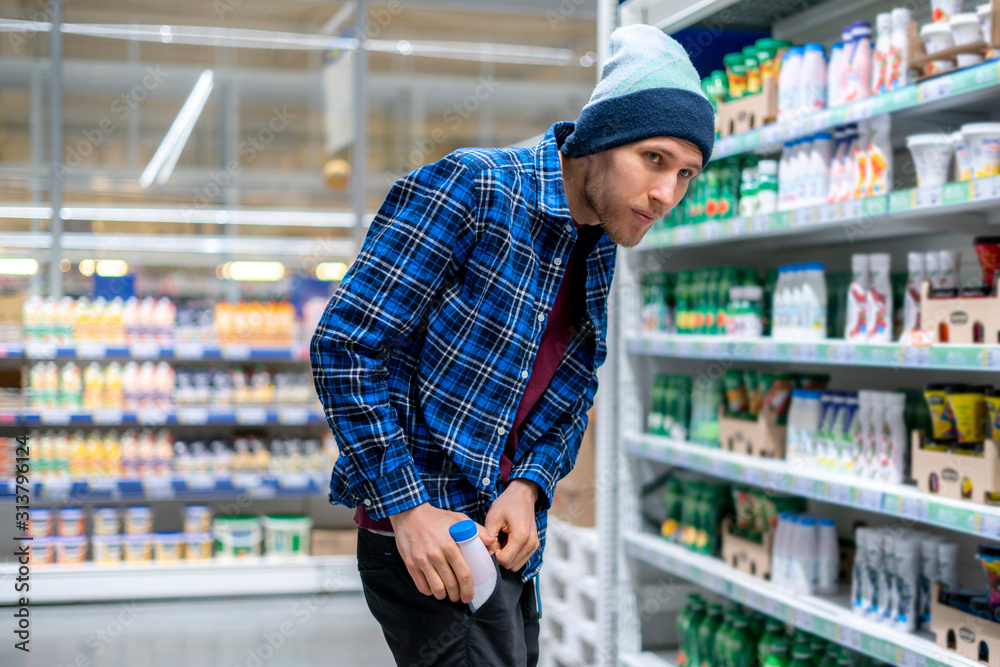 Fototapeta the kleptomania concept, a man in the grocery store stealing food and put it in the pocket