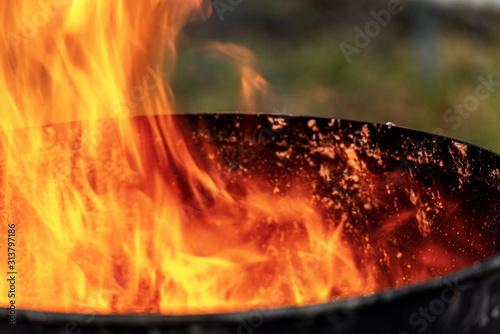 Obraz Close-up of flames in an old blackened metal bin - fototapety do salonu