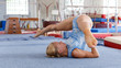 Sporty female gymnast in bodysuit during workout in sport gym
