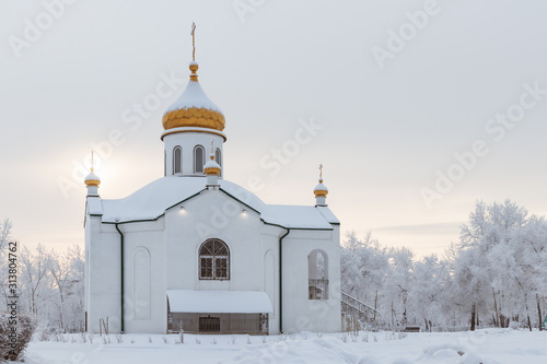 Fototapeta Winter landscape - a small Orthodox church with a ray of sunshin obraz