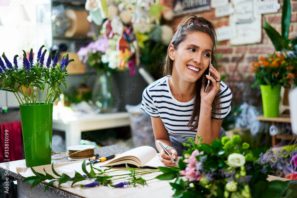 Fototapeta Cheerful florist on phone with client and writing down their order