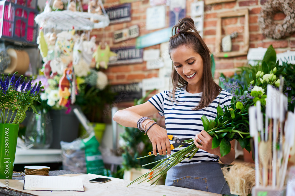 Fototapeta Cheerful young florist cutting flowers for bouquet at the counter