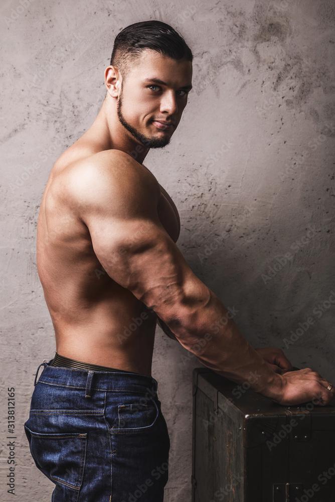 Fototapeta Massive bodybuilder posing beside the concrete wall