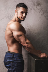 Massive bodybuilder posing beside the concrete wall