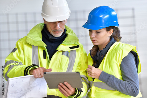 Photo Instructor with apprentice on construction site working with tablet