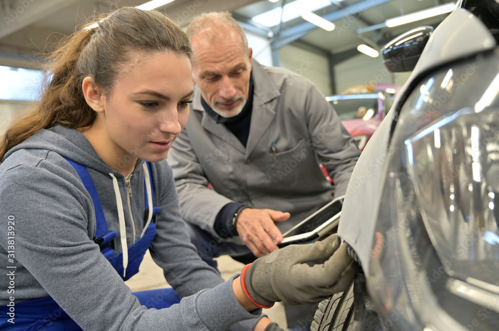 Fototapeta Apprentice with instructor working on vehicle